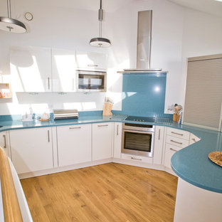 Inspiration for a nautical u-shaped kitchen/diner in Cornwall with a submerged sink, flat-panel cabinets, white cabinets, quartz worktops, blue splashback, stone slab splashback, stainless steel appliances and blue worktops.