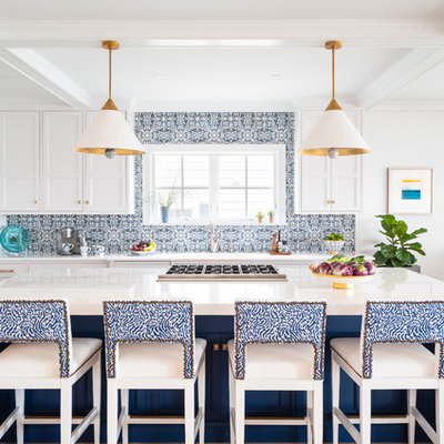 Example of a mid-sized beach style l-shaped light wood floor and brown floor eat-in kitchen design in Philadelphia with shaker cabinets, blue backsplash, stainless steel appliances, an island, white countertops, a farmhouse sink, white cabinets, quartzite countertops and ceramic backsplash
