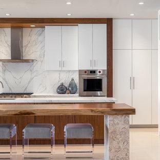 マイアミの大きいコンテンポラリースタイルのおしゃれなキッチン (アンダーカウンターシンク、フラットパネル扉のキャビネット、白いキャビネット、大理石カウンター、白いキッチンパネル、大理石の床、パネルと同色の調理設備、ライムストーンの床、ベージュの床) の写真