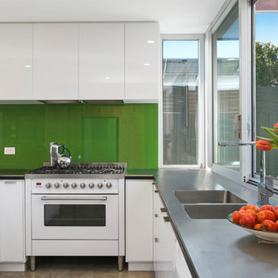 Contemporary eat-in kitchen pictures - Eat-in kitchen - contemporary u-shaped eat-in kitchen idea in Other with a drop-in sink, white cabinets, green backsplash, glass sheet backsplash, no island, gray countertops, flat-panel cabinets, zinc countertops and stainless steel appliances