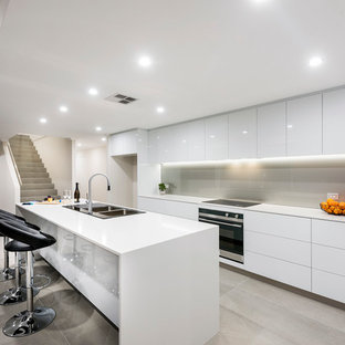 Large contemporary galley kitchen in Perth with a double-bowl sink, flat-panel cabinets, white cabinets, quartz benchtops, with island, grey floor, white benchtop, grey splashback and glass sheet splashback.