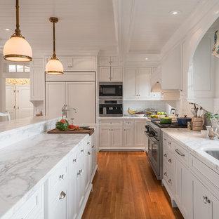 ポートランド(メイン)の大きいビーチスタイルのおしゃれなキッチン (アンダーカウンターシンク、白いキャビネット、大理石カウンター、落し込みパネル扉のキャビネット、白いキッチンパネル、サブウェイタイルのキッチンパネル、パネルと同色の調理設備、無垢フローリング、オレンジの床) の写真