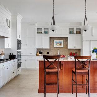 Large transitional l-shaped separate kitchen in Boston with white cabinets, granite benchtops, glass tile splashback, porcelain floors, a single-bowl sink, raised-panel cabinets, metallic splashback, panelled appliances, multiple islands and beige floor.