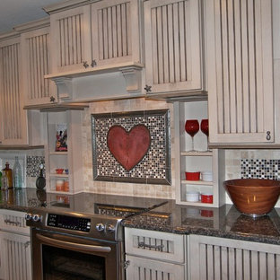 Photo of a mid-sized transitional l-shaped eat-in kitchen in Miami with a farmhouse sink, louvered cabinets, beige cabinets, granite benchtops, multi-coloured splashback, mosaic tile splashback, stainless steel appliances, porcelain floors and with island.