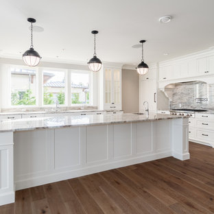 Large traditional u-shaped eat-in kitchen in Vancouver with an undermount sink, recessed-panel cabinets, white cabinets, limestone benchtops, multi-coloured splashback, stone slab splashback, stainless steel appliances, medium hardwood floors, with island, brown floor and multi-coloured benchtop.
