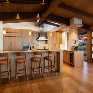 Exemple d'une cuisine ouverte linéaire moderne de taille moyenne avec un évier 1 bac, un placard à porte plane, des portes de placard en bois clair, un plan de travail en granite, une crédence multicolore, une crédence en carreau de verre, un électroménager encastrable, un sol en bambou et un îlot central.
