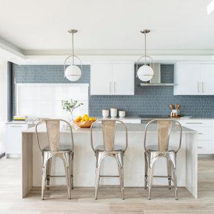 Moderne Küche in L-Form mit Unterbauwaschbecken, flächenbündigen Schrankfronten, weißen Schränken, Küchenrückwand in Blau, Elektrogeräten mit Frontblende, hellem Holzboden, Kücheninsel, beigem Boden, beiger Arbeitsplatte und eingelassener Decke in Miami
