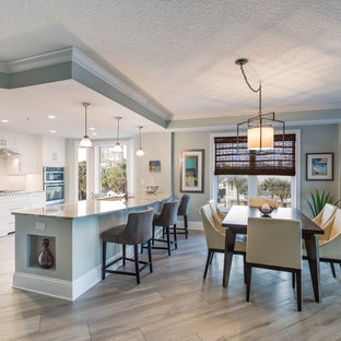 Photo of a beach style kitchen in Jacksonville with an undermount sink, ceramic floors, grey floor, shaker cabinets, white cabinets, granite benchtops, white splashback, limestone splashback, stainless steel appliances, with island and brown benchtop.