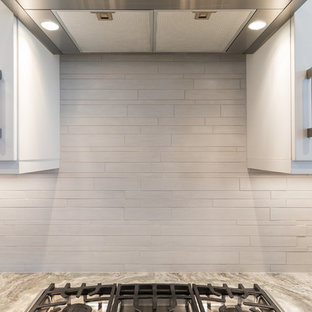 This is an example of a beach style kitchen in Jacksonville with an undermount sink, shaker cabinets, white cabinets, granite benchtops, white splashback, limestone splashback, stainless steel appliances, ceramic floors, with island, grey floor and brown benchtop.