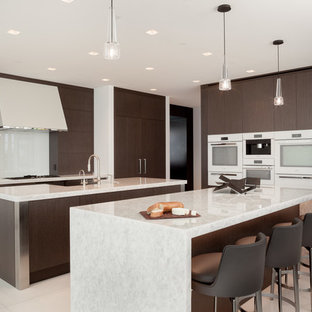 Photo of a large contemporary kitchen in Miami with flat-panel cabinets, recycled glass benchtops, white splashback, white appliances, marble floors, multiple islands, white floor, dark wood cabinets, glass sheet splashback and white benchtop.