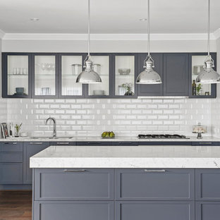 Design ideas for a transitional galley kitchen in Melbourne with an undermount sink, shaker cabinets, grey cabinets, white splashback, subway tile splashback, medium hardwood floors, with island, brown floor and white benchtop.