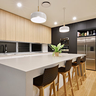 Inspiration for a beach style l-shaped kitchen in Sunshine Coast with a double-bowl sink, flat-panel cabinets, light wood cabinets, window splashback, stainless steel appliances, medium hardwood floors, with island and brown floor.