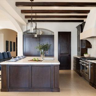Offene, Zweizeilige, Große Mediterrane Küche mit Unterbauwaschbecken, Schrankfronten mit vertiefter Füllung, dunklen Holzschränken, Mineralwerkstoff-Arbeitsplatte, Küchenrückwand in Beige, Kalk-Rückwand, Elektrogeräten mit Frontblende, Kalkstein, Kücheninsel, beigem Boden, beiger Arbeitsplatte und freigelegten Dachbalken in Los Angeles