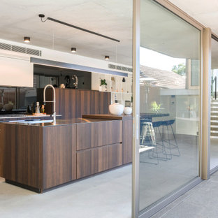 Inspiration for a large contemporary l-shaped eat-in kitchen in Sydney with an undermount sink, flat-panel cabinets, medium wood cabinets, black splashback, glass sheet splashback, panelled appliances, porcelain floors, with island, grey floor and beige benchtop.