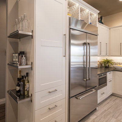 Example of a mid-sized transitional u-shaped porcelain tile open concept kitchen design in Phoenix with a farmhouse sink, shaker cabinets, white cabinets, solid surface countertops, white backsplash, subway tile backsplash, stainless steel appliances and an island