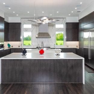 Esempio di una cucina design con ante lisce, ante in legno bruno, paraspruzzi bianco, paraspruzzi in lastra di pietra, elettrodomestici in acciaio inossidabile, parquet scuro, 2 o più isole, pavimento marrone e top bianco
