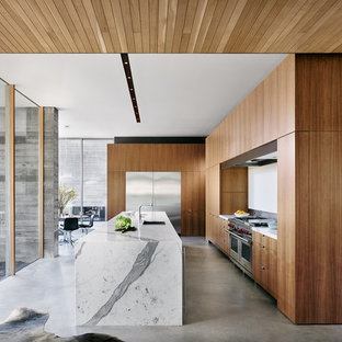 Large modern open concept kitchen designs - Inspiration for a large modern concrete floor and gray floor open concept kitchen remodel in Austin with flat-panel cabinets, medium tone wood cabinets, an island, an undermount sink, stainless steel appliances and white countertops