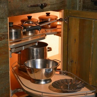 This is an example of a large rustic u-shaped kitchen pantry in New York with a submerged sink, green cabinets, granite worktops, white appliances, medium hardwood flooring, a breakfast bar and shaker cabinets.