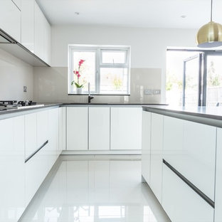 Photo of a contemporary l-shaped kitchen in London with a built-in sink, flat-panel cabinets, white cabinets, grey splashback, glass sheet splashback, integrated appliances, an island, white floors and grey worktops.