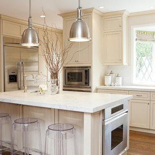 Ispirazione per una cucina tradizionale con ante con riquadro incassato, ante beige, top in marmo, paraspruzzi bianco e elettrodomestici in acciaio inossidabile