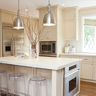 Traditional kitchen in San Francisco with recessed-panel cabinets, beige cabinets, marble worktops, white splashback and stainless steel appliances.