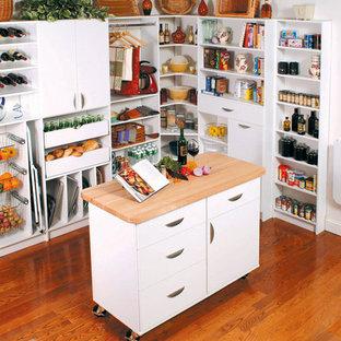 ニューヨークの大きいトラディショナルスタイルのおしゃれなキッチン (フラットパネル扉のキャビネット、白いキャビネット、木材カウンター、無垢フローリング) の写真
