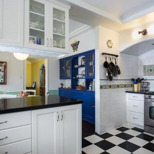Foto på ett mellanstort vintage kök, med skåp i shakerstil, vita skåp, bänkskiva i kvarts, flerfärgad stänkskydd, stänkskydd i keramik, rostfria vitvaror, vinylgolv och en halv köksö