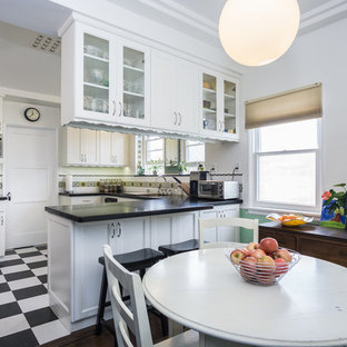 Inspiration for a mid-sized traditional u-shaped eat-in kitchen in Los Angeles with an undermount sink, white cabinets, quartz benchtops, multi-coloured splashback, ceramic splashback, stainless steel appliances, vinyl floors, a peninsula and glass-front cabinets.