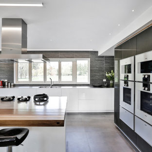 Design ideas for an expansive contemporary single-wall open plan kitchen in Christchurch with an integrated sink, glass-front cabinets, white cabinets, stainless steel benchtops, grey splashback, porcelain splashback, stainless steel appliances, porcelain floors, with island and grey floor.