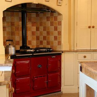 Geschlossene, Zweizeilige, Große Klassische Küche mit Landhausspüle, Schrankfronten im Shaker-Stil, beigen Schränken, bunten Elektrogeräten und Kücheninsel in Wiltshire