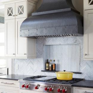 Idee per una grande cucina tradizionale con ante in stile shaker, ante bianche, top in granito, paraspruzzi grigio, paraspruzzi con piastrelle in pietra, elettrodomestici in acciaio inossidabile, parquet scuro, isola e top nero
