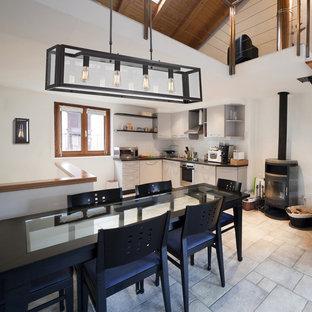 ニューヨークの大きいエクレクティックスタイルのおしゃれなキッチン (ドロップインシンク、フラットパネル扉のキャビネット、白いキャビネット、木材カウンター、ベージュキッチンパネル、セラミックタイルのキッチンパネル、白い調理設備、セラミックタイルの床) の写真