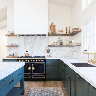 Diseño de cocina en L, marinera, con fregadero bajoencimera, armarios con paneles empotrados, puertas de armario verdes, salpicadero verde, electrodomésticos negros, suelo de madera clara, una isla y suelo beige
