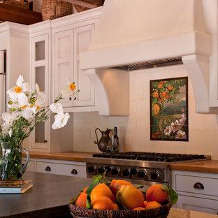 ロサンゼルスの中くらいのカントリー風おしゃれなキッチン (落し込みパネル扉のキャビネット、白いキャビネット、御影石カウンター、ベージュキッチンパネル、石タイルのキッチンパネル、シルバーの調理設備、セラミックタイルの床) の写真