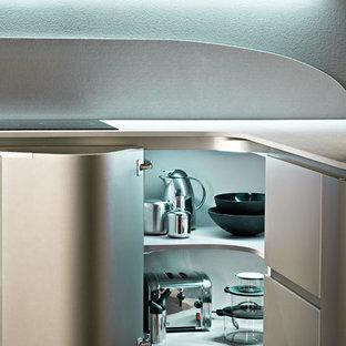 Immagine di una cucina moderna con lavello sottopiano, ante lisce, ante beige, paraspruzzi nero, elettrodomestici in acciaio inossidabile, parquet scuro, penisola e pavimento nero