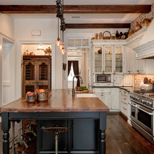 Farmhouse kitchen pictures - Kitchen - cottage u-shaped medium tone wood floor and brown floor kitchen idea in Jacksonville with a farmhouse sink, raised-panel cabinets, black cabinets, wood countertops, red backsplash, brick backsplash, stainless steel appliances, an island and brown countertops