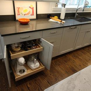 デトロイトの大きいエクレクティックスタイルのおしゃれなキッチン (シェーカースタイル扉のキャビネット、グレーのキャビネット、クオーツストーンカウンター、シルバーの調理設備の、アンダーカウンターシンク、白いキッチンパネル、濃色無垢フローリング、茶色い床、グレーのキッチンカウンター) の写真