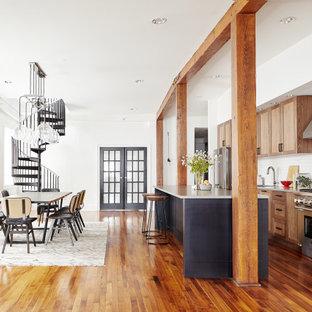 フィラデルフィアの中くらいのコンテンポラリースタイルのおしゃれなキッチン (アンダーカウンターシンク、シェーカースタイル扉のキャビネット、中間色木目調キャビネット、クオーツストーンカウンター、白いキッチンパネル、レンガのキッチンパネル、シルバーの調理設備、無垢フローリング、茶色い床、グレーのキッチンカウンター) の写真