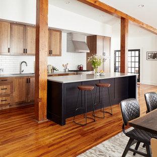 フィラデルフィアの中サイズのコンテンポラリースタイルのおしゃれなキッチン (アンダーカウンターシンク、シェーカースタイル扉のキャビネット、中間色木目調キャビネット、クオーツストーンカウンター、白いキッチンパネル、レンガのキッチンパネル、シルバーの調理設備の、無垢フローリング、茶色い床、グレーのキッチンカウンター) の写真