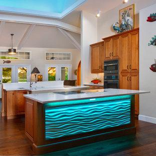 マイアミの大きいトロピカルスタイルのおしゃれなキッチン (レイズドパネル扉のキャビネット、中間色木目調キャビネット、クオーツストーンカウンター、シルバーの調理設備の、無垢フローリング、茶色い床、白いキッチンカウンター) の写真