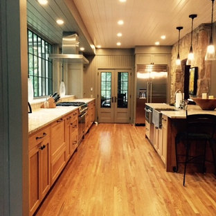 Inspiration for a large country galley open plan kitchen in Other with a farmhouse sink, shaker cabinets, medium wood cabinets, limestone benchtops, stainless steel appliances, medium hardwood floors and with island.