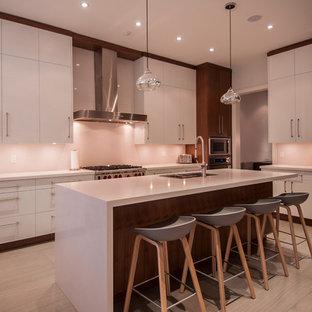 トロントの大きいモダンスタイルのおしゃれなキッチン (アンダーカウンターシンク、フラットパネル扉のキャビネット、白いキャビネット、シルバーの調理設備の、セラミックタイルの床、御影石カウンター、白いキッチンパネル、石スラブのキッチンパネル、白い床) の写真