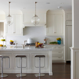 Beach style kitchen in New York with an undermount sink, recessed-panel cabinets, white cabinets, white splashback and panelled appliances.