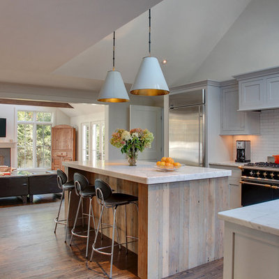 Mid-sized transitional l-shaped medium tone wood floor open concept kitchen photo in New York with an undermount sink, recessed-panel cabinets, gray cabinets, marble countertops, white backsplash, subway tile backsplash, stainless steel appliances and an island