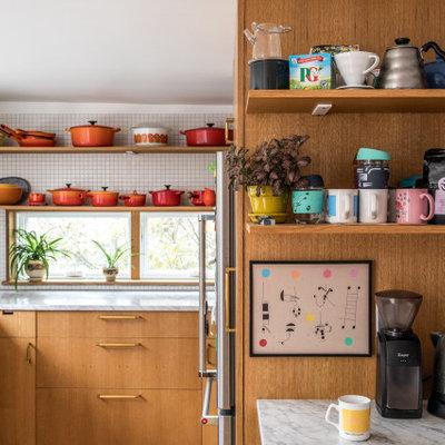 Mid-sized mid-century modern u-shaped kitchen photo in Portland Maine with flat-panel cabinets, medium tone wood cabinets, marble countertops, white backsplash, ceramic backsplash, stainless steel appliances, gray countertops and a peninsula