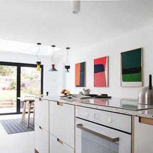 Esempio di una cucina moderna di medie dimensioni con lavello sottopiano, ante lisce, ante bianche, top alla veneziana, paraspruzzi bianco, elettrodomestici in acciaio inossidabile, pavimento in cemento, isola, pavimento grigio e top bianco