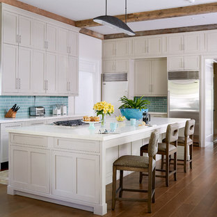 Kitchen - traditional medium tone wood floor kitchen idea in Other with a farmhouse sink, shaker cabinets, beige cabinets, blue backsplash, subway tile backsplash, stainless steel appliances and an island