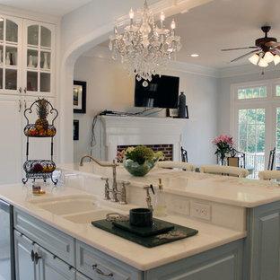 ローリーの中サイズのシャビーシック調のおしゃれなキッチン (ダブルシンク、レイズドパネル扉のキャビネット、白いキャビネット、珪岩カウンター、白いキッチンパネル、ガラスタイルのキッチンパネル、シルバーの調理設備の、レンガの床) の写真