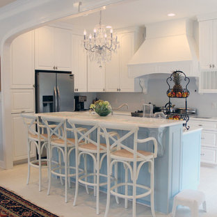 Design ideas for a mid-sized shabby-chic style l-shaped open plan kitchen in Raleigh with a double-bowl sink, raised-panel cabinets, white cabinets, quartzite benchtops, white splashback, glass tile splashback, stainless steel appliances, with island and brick floors.