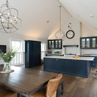 Photo of a large rustic single-wall kitchen/diner in Other with a belfast sink, glass-front cabinets, blue cabinets, quartz worktops, white splashback, metro tiled splashback, stainless steel appliances, dark hardwood flooring, an island, brown floors and white worktops.
